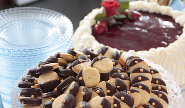 Ylioppilasjuhlien kahvipöydässä pikkuleipiä ja täytekakkua