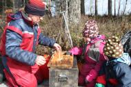 Pienet retkeläiset katsomassa kun loimukaloja kiinnitetään loimulautoihin